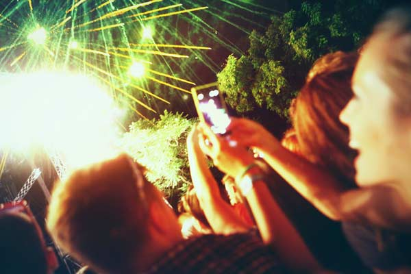 smiling people taking video of fireworks
