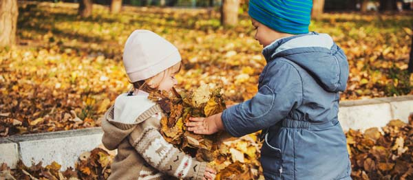 kids in warm coats playing in the leaves